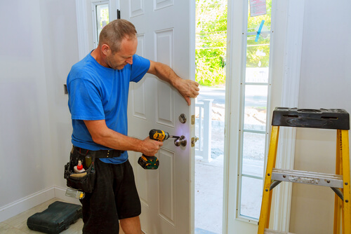 Man using power drill on door knob