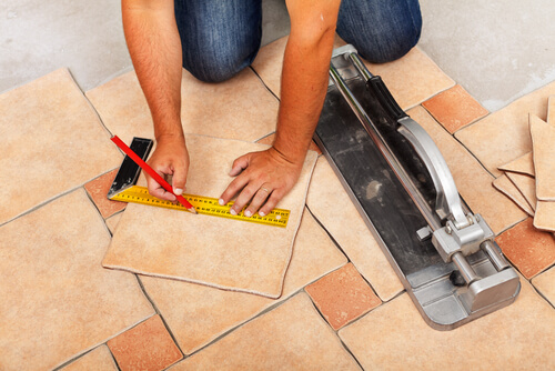 Man measuring length of tile