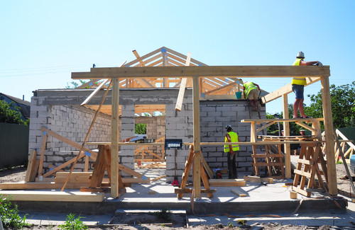Three man construction wooden frame of house