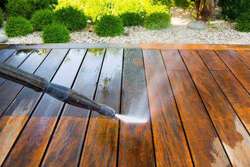 Power washing wooden floor of porch outside
