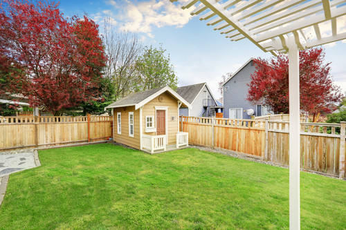 Shed with windows and railing in backyard