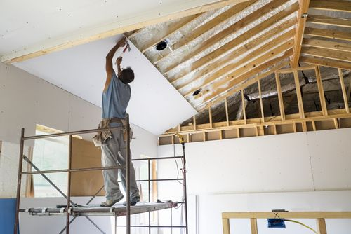 Man putting on underside of roof sheetrock